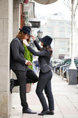 Young happy stylish couple in black hats posing on the street — Stock Photo