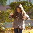 Young beautiful little girl with yellow leaves in autumn park — Stock Photo #54248879