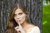 Woman has put forefinger to lips as sign of silence — Stock Photo