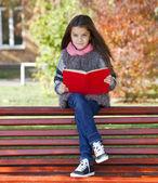 Красивая девочка, сидя на скамейке — Стоковое фото