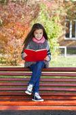 Bella bambina, seduta su una panchina — Foto Stock
