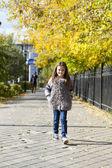 Little girl walking on autumn street — Stock Photo