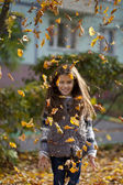 Young beautiful little girl with yellow leaves in autumn park — Foto de Stock