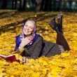 Beautiful young girl lying on autumn leaves with red book — Stock Photo #55396501