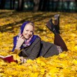 Beautiful young girl lying on autumn leaves with red book — Stock Photo #55396511