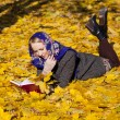 Beautiful young girl lying on autumn leaves with red book — Stock Photo #55396517