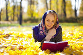 Beautiful young girl lying on autumn leaves with red book — Stock Photo
