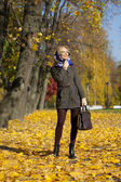 Young woman walking in autumn park — Stock Photo