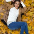 Young beautiful girl in blue jeans lying on yellow leaves — Stock Photo #55573427