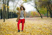 Young woman in fashion coat walking in autumn park — Stock Photo