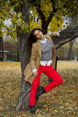 Young woman in fashion coat walking in autumn park — Stok fotoğraf