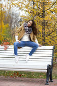 Beautiful woman sitting on a bench in autumn park — Stockfoto