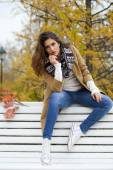 Beautiful woman sitting on a bench in autumn park — Stok fotoğraf