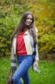 молодая женщина в пальто моды, идущем в осеннем парке — Стоковое фото