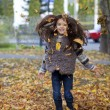 Young beautiful little girl with yellow leaves in autumn park — Stock Photo #55760133