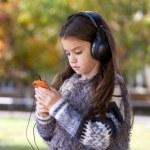 Beautiful little girl listening to music on headphones — Stock Photo #55760425