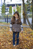 Young beautiful little girl with yellow leaves in autumn park — Stock Photo