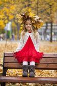 Piękna dziewczynka siedzi na ławce — Zdjęcie stockowe