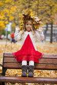 Beautiful little girl sitting on a bench  — Stock Photo
