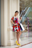 Beautiful woman in red flowers dress in the shop — Stock Photo