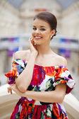 Beautiful woman in red flowers dress in the shop — Foto de Stock