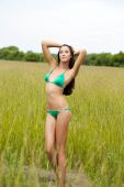 Beautiful model in a green bathing suit standing in the summer f — Stock Photo