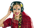 Beautiful Indian woman listening to music on headphones — Stockfoto