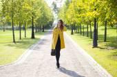 Mutlu bir kadın sarı montlu sonbahar street yürüyüş — Stok fotoğraf