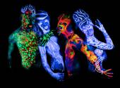 Four - Body art glowing in ultraviolet light — Stock Photo
