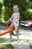 Adorable little girl having fun on a swing outdoor  — Foto de Stock