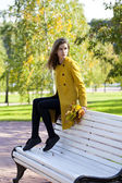 Beautiful woman sitting on a bench in autumn park — Stock Photo