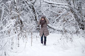Happy little girl on the background of a winter park — Stockfoto