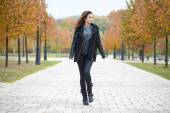 Happy woman in black coat walking autumn street — Stock Photo