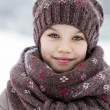 Happy little girl on the background of a winter park — Stock Photo #61907563