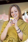 Szczęśliwa młoda kobieta czytanie wiadomości w telefonie — Zdjęcie stockowe