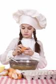 Little cook girl in a white apron breaks eggs in a deep dish — Stock Photo