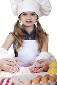 Little girl in a white apron and chefs hat knead the dough in th — Stock Photo