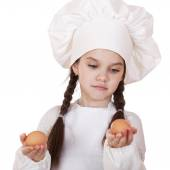 Portrait of a little girl in a white apron holding two chicken e — Stock Photo