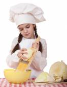 Portrait of a little girl in a white apron and chefs hat shred c — Stok fotoğraf