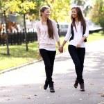 Fashionable girls twins walk in the street — Stock Photo #69145301