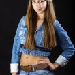 Portrait young girl in a blue jeans jacket and shorts in dark st — Stock Photo #69653433