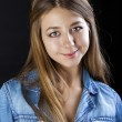 Portrait young girl in a blue jeans jacket in dark studio — Stock Photo #69653459