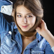 Portrait young girl in a blue jeans jacket in dark studio — Stock Photo #69653465
