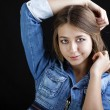 Portrait young girl in a blue jeans jacket in dark studio — Stock Photo #69654577