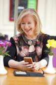 Mature blonde woman reads the message on the phone while sitting — ストック写真