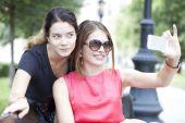Sorridente giovani ragazze con cellulare seduti su una panchina in un parco — Foto Stock