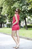 Street fashion. Young woman in red shorts and a blouse — Stock Photo