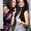 Two young women talking on payphone — Stock Photo #70490215