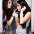 Two young women talking on payphone — Stock Photo #70490309