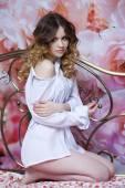 Beautiful blonde woman on bed, wearing white large casual shirt — Foto Stock